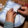 A l'aide du stylet, on coince les morceaux de tissus dans les trous en respectant le code couleur